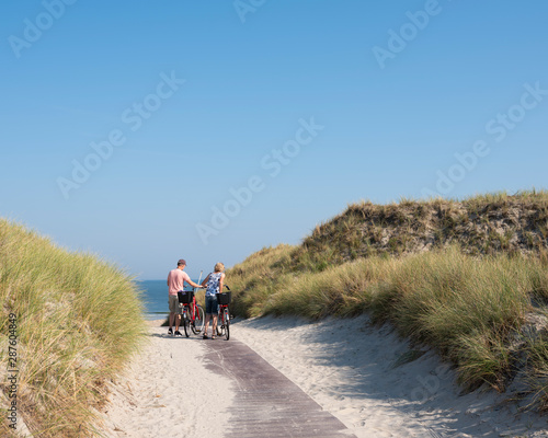Fotografie, Obraz  couple with bicycles at top of dunes near sea on german island of norderney on s