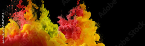 Acrylic red, yellow colors in water. Ink blot. Abstract black background.