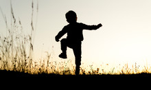 Silhouete Of Small Boy Running...