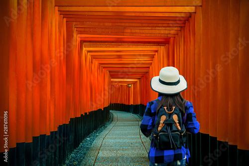 Woman traveler with backpack at fushimi inari taisha shrine in Kyoto, Japan.
