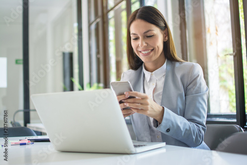 Fotografiet  Beautiful young business woman using phone near laptop in office