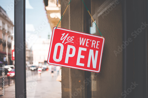 Obraz yes we're open sign on the glass of the doors in store.  welcome sign at the store - fototapety do salonu