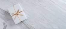 Top View Of Gift Box With Gold Ribbon On White Marble Background.