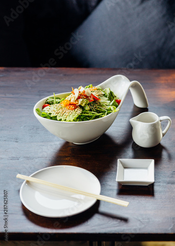 Japanese salad with avocado, tomato, green oak, almond and sesame topping sesame salad dressing.