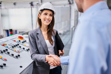 Woman Wearing Hard Hat At Control Panel In A Factory Shaking Hands With Businessman