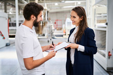 Employee Signing Document In Factory Held By Businesswoman