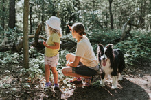 Mother With Daughter And Dog In A Forest