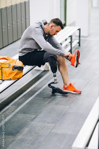 Obraz na plátně  Athlete man with prosthetic leg in gym locker room preparing to train