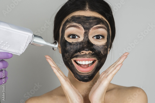 Photo Asian woman with black mask on face with surprised emotionon, advertising proced