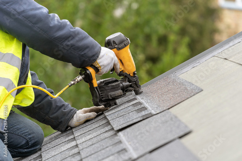 Obraz na płótnie Workman using pneumatic nail gun install tile on roof of new house under constru