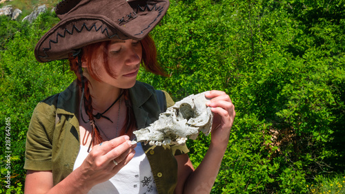 A beautiful archaeologist girl in a cowboy hat examines the skull of a domestic pig or wild boar near the settlements of the ancient people of cave cities Canvas Print