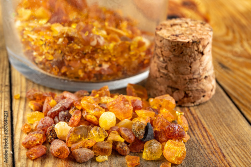 Small raw amber in a glass bottle on a wooden table Fotobehang