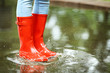 Leinwanddruck Bild Woman with red rubber boots in puddle, closeup. Rainy weather