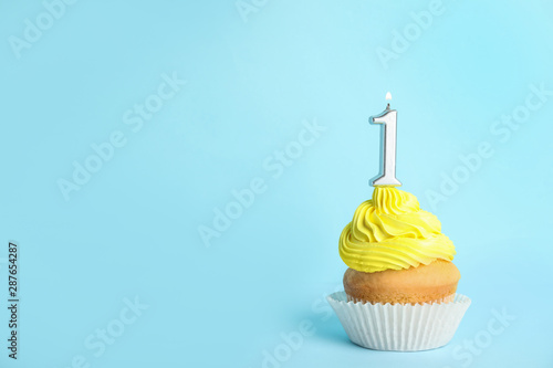 Photo  Birthday cupcake with number one candle on blue background, space for text