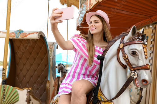 Slika na platnu Young pretty woman taking selfie on carousel in amusement park