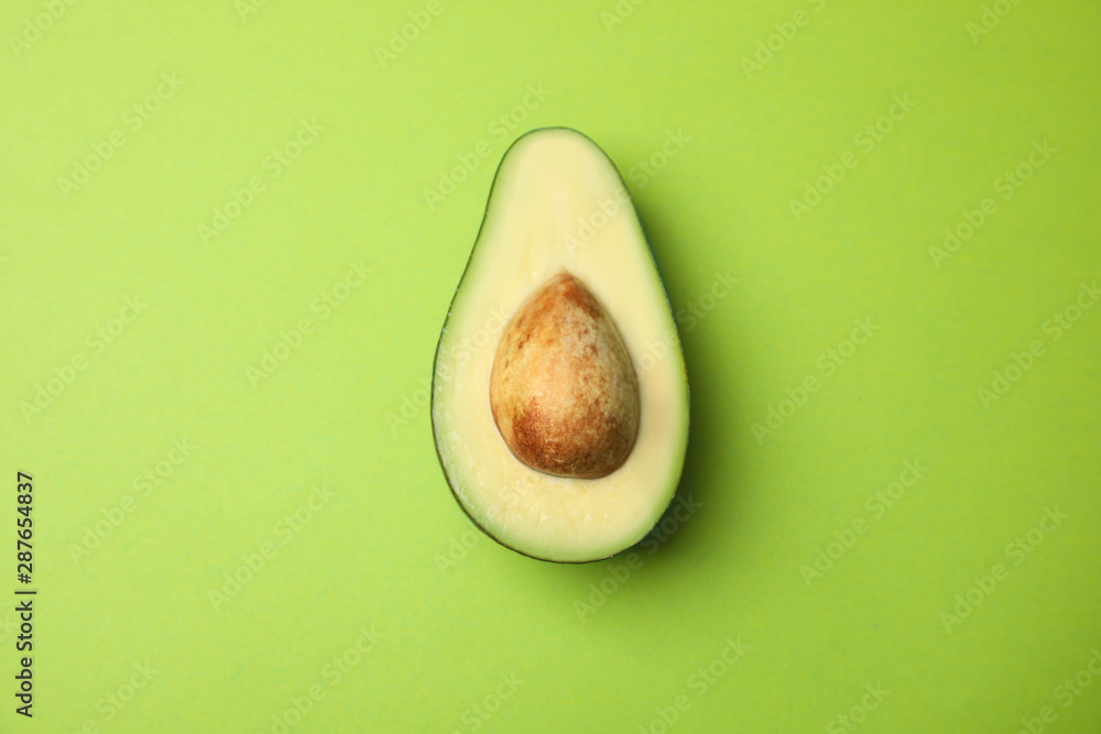 Fototapety, obrazy: Cut fresh ripe avocado on green background, top view
