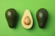 Leinwanddruck Bild - Cut and whole fresh ripe avocados on green background, flat lay