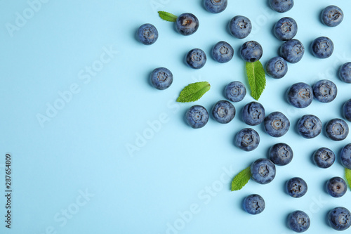 Tasty ripe blueberries and leaves on blue background, flat lay with space for te Fototapete