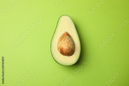 Stampa su Tela Cut fresh ripe avocado on green background, top view