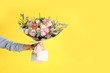 Leinwandbild Motiv Man holding beautiful flower bouquet on yellow background, closeup view. Space for text