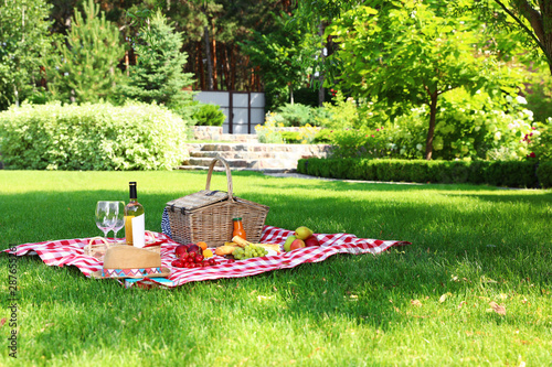 Photo sur Toile Pique-nique Picnic basket with products and bottle of wine on checkered blanket in garden. Space for text
