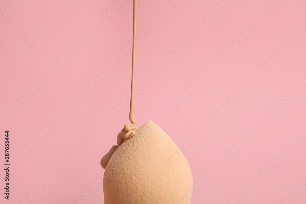 Fototapeta Liquid foundation pouring on makeup sponge against pink background