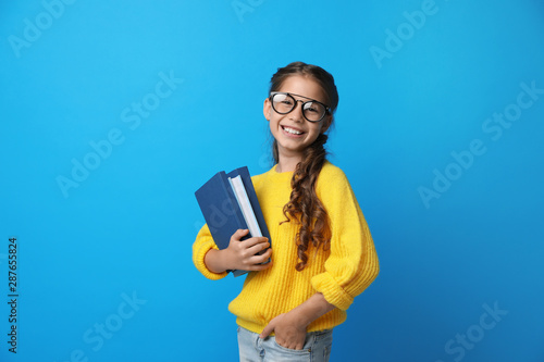 Fotomural  Cute little girl with glasses and books on blue background