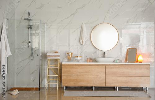Stampa su Tela  Modern bathroom interior with shower stall, vessel sink and round mirror