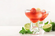 Glass Of Melon And Watermelon Ball Cocktail On White Wooden Table. Space For Text