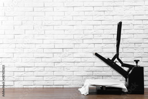 Heat press machine with t-shirt on wooden table near white brick wall, space for Canvas Print