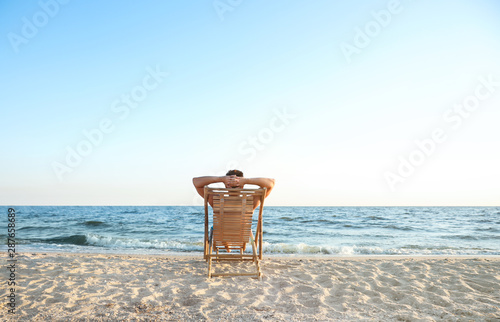 Obraz Young man relaxing in deck chair on beach near sea - fototapety do salonu