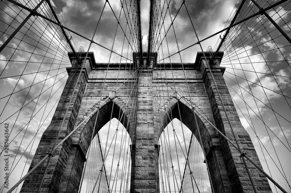 Fototapeta Scenic view of the architectural details of the Brooklyn Bridge in New York City in dramatic black and white monochrome under moody overcast skies