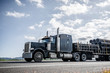canvas print picture - Black big rig semi truck transporting plastic pipes on step down semi trailer running on the road according to the given route