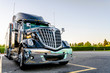 canvas print picture - Black stylish big rig semi truck with semi trailer standing in the truck stop parking lot for rest