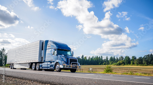 Fotomural  Blue big rig semi truck with grille guard trabsporting frozen cargo in refrigera