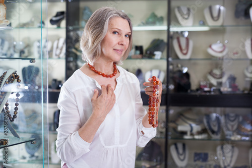 Fotografie, Tablou  Adult woman chooses cornelian agate jewelry in the store