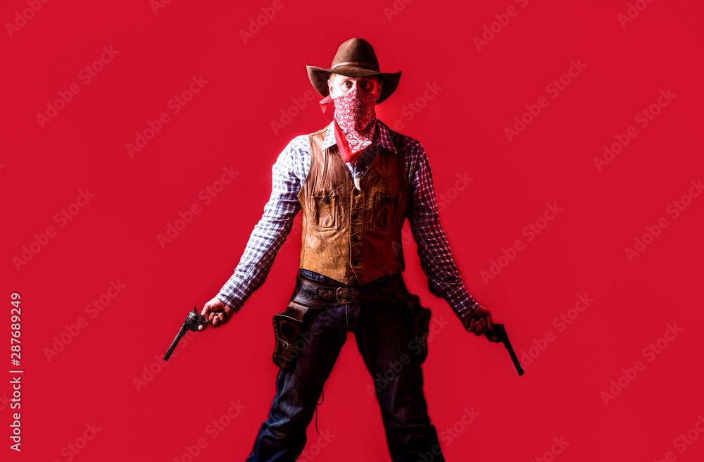 Fototapeta Man wearing cowboy hat, gun. West, guns. Portrait of a cowboy. owboy with weapon on red background. American bandit in mask, western man with hat. Portrait of farmer or cowboy in hat