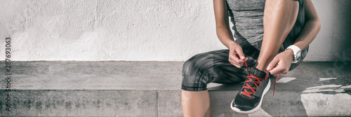 Runner athlete woman getting ready to run tying running shoes laces at gym for cardio workout healthy active lifestyle background panorama banner.