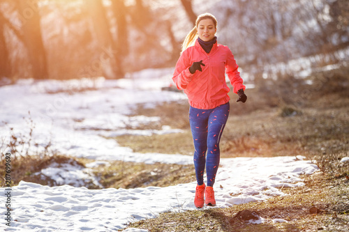Foto  Young slim woman jogging in winter park