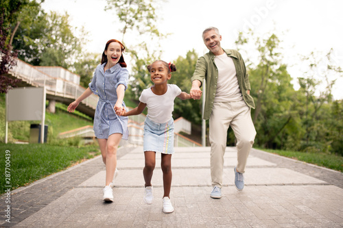 African-American daughter running while walking with parents Wallpaper Mural