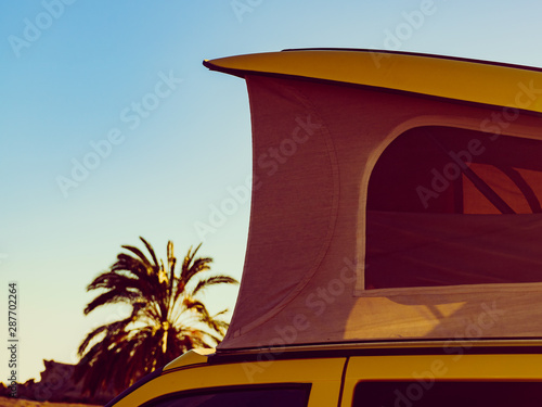 Camper van with tent on roof on beach Tablou Canvas