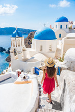 Travel Europe Tourist Girl Walking In Santorini Stairs Of City Streets, Famous European Destination Three Blue Domes, Famous Greek Landmark. Oia Village, Santorini Island, Luxury Vacation.
