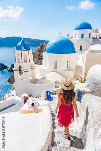 Travel Europe tourist girl walking in Santorini stairs of city streets, famous european destination three blue domes, famous Greek landmark Wallpaper Mural