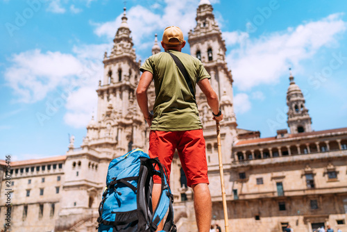 Canvas Print Young backpacker man pilgrim standing on the Obradeiro square (plaza) - the main square in Santiago de Compostela as a end of his Camino de Santiago pilgrimage