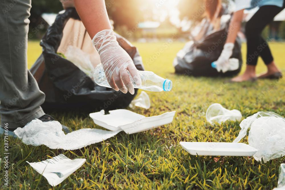 Fototapeta mother and children keeping garbage plastic bottle into black bag at park in morning light
