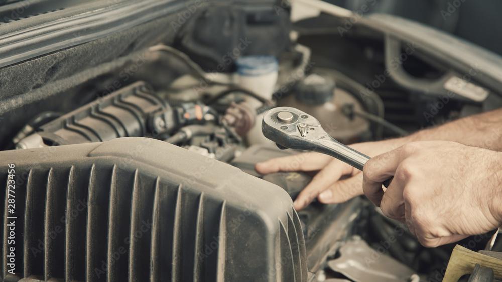 Fototapeta Mechantroniker repariert Motor von Auto