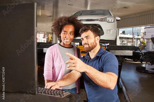 Fototapeta Mechatroniker erklärt Kundin Auto Diagnose Check