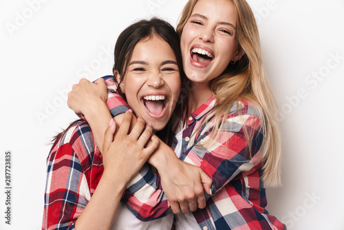 Cheerful happy optimistic young pretty girls friends sisters posing isolated over white wall background hugging Tablou Canvas