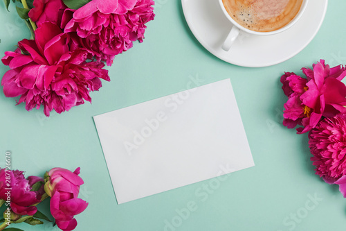 La pose en embrasure Fleur Blank card mock-up on the table with beautiful peonies and cup of coffee