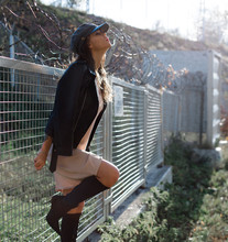 Sensual Young Woman Posing Outdoors.  Holding Chain-link Fence. Cheers Freedom Concept